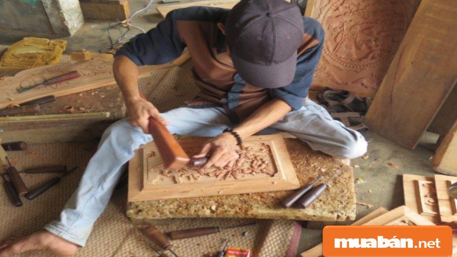 Thợ mộc đang chạm trổ, khắc họa tiết vào một sản phẩm gỗ.